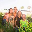 Familienbild mit Geschwistern in der Sonne draußen auf dem Feld